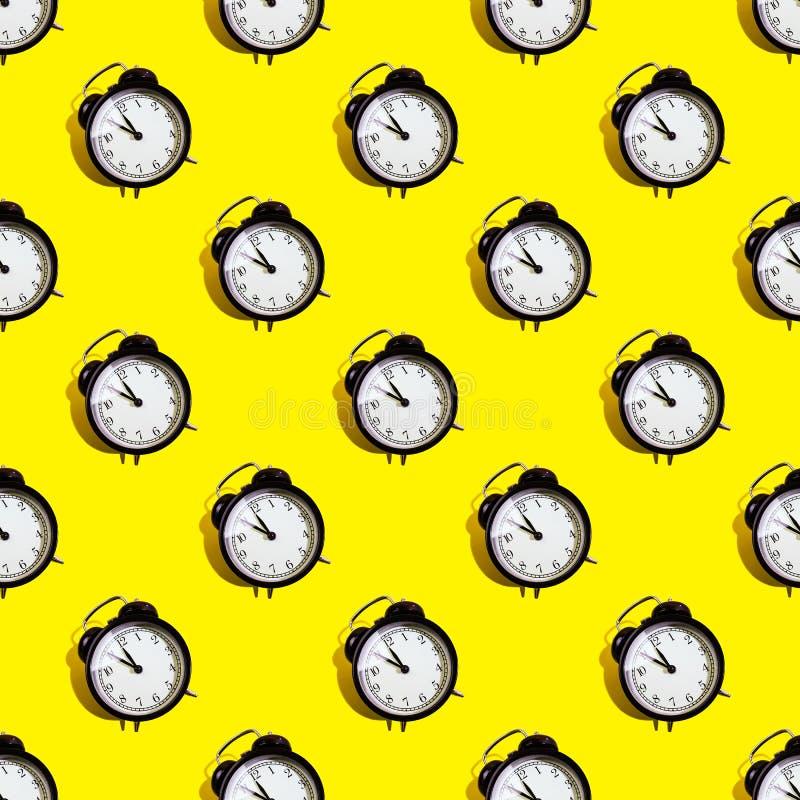 Many black classic style alarm clock isolated on yellow background. Many black classic style alarm clock with hard shadow isolated on yellow background. Smile royalty free stock photography
