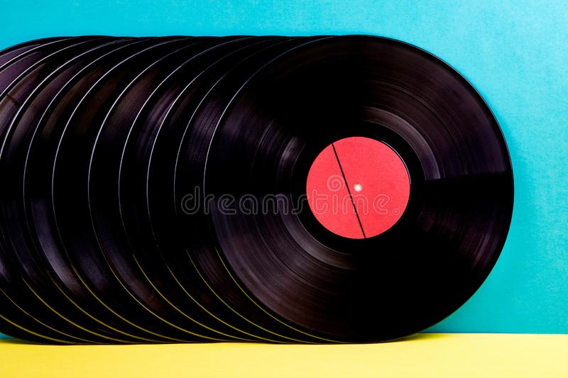 Vinyl discs on background. Many black colored vinyl discks placed  in a  line on yellow and blue background royalty free stock images