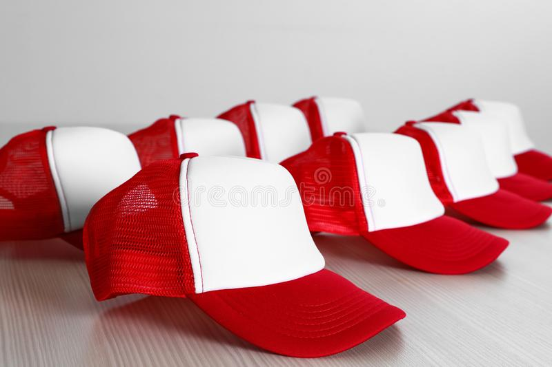 Many blank colorful caps on wooden table near light wall. Mock up for design stock images