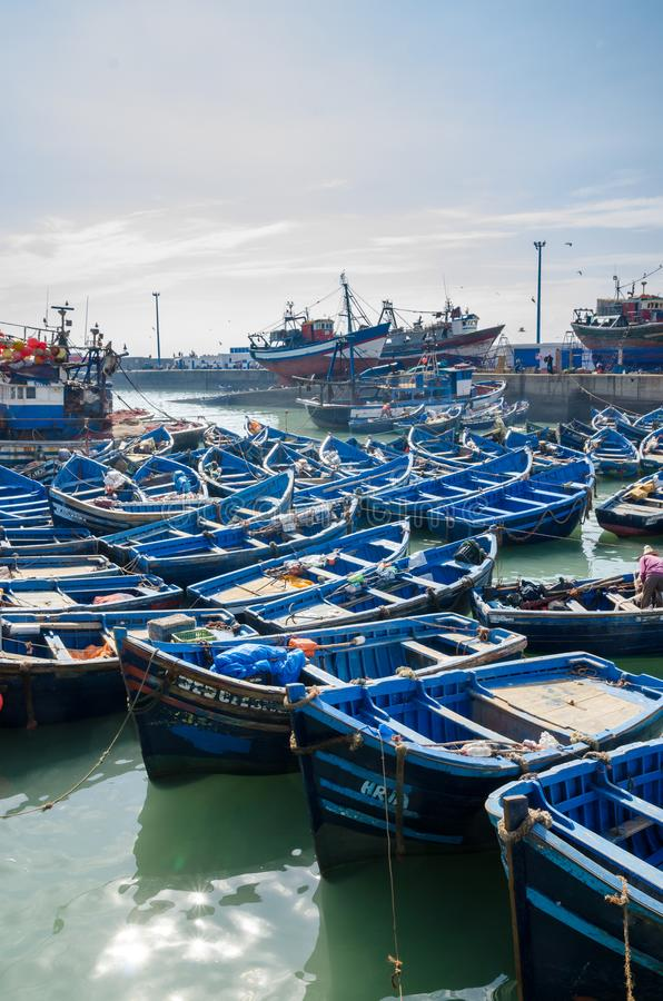 Many blue wooden fishing boats anchored in historic port of medieval town Essaouira, Morocco, North Africa royalty free stock photography