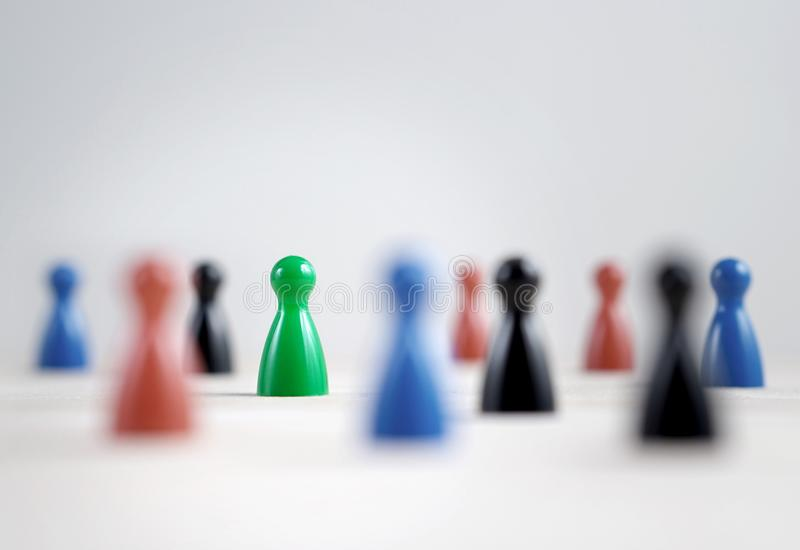 Many board game pawns on table, selective focus on the green one royalty free stock image