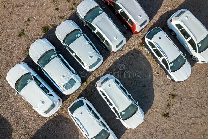 Many brand new cars covered in protective foil on sale parked outside on dealer parking lot stock photography