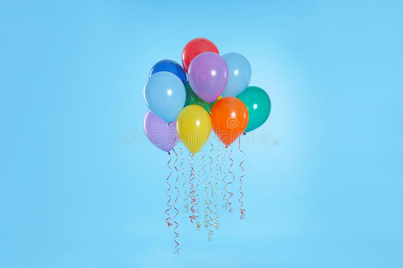 Many bright balloons floating. On color background royalty free stock photo
