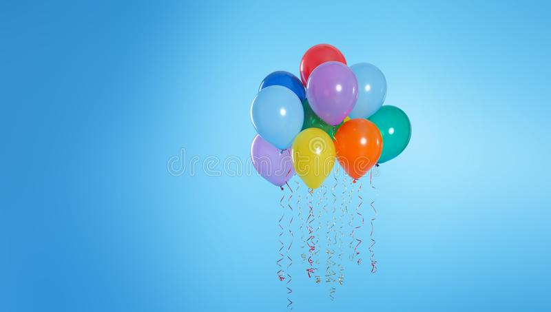 Many bright balloons floating on color background. Space for text stock photos