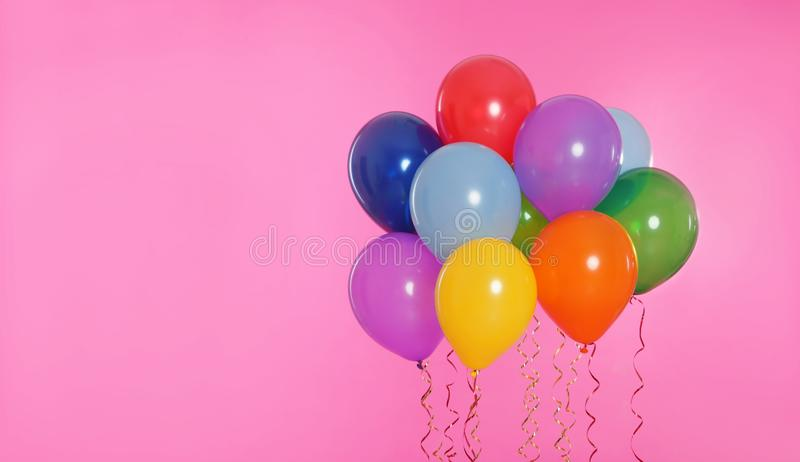 Many bright balloons floating. On color background stock images