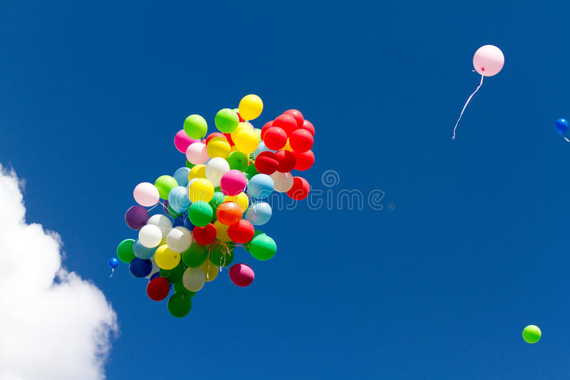 Many bright baloons in the blue sky royalty free stock photography