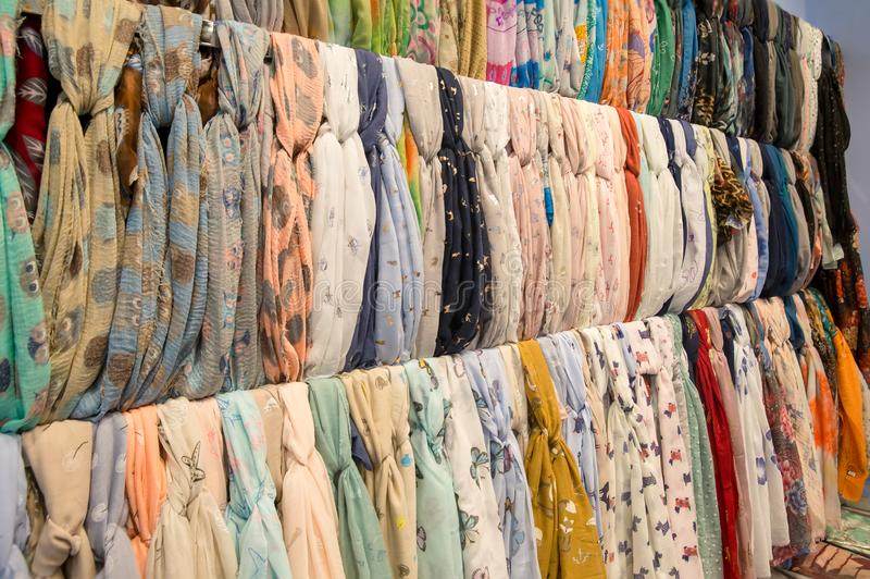 Many bright female scarfs and shawl. colorful scarves hanging in the market. clothes rack with a selection of scarves or scarfs. stock photos