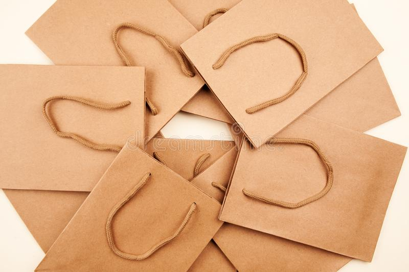 Many brown paper bags with handles closeup shot. Purchase, gift, buy, commerce, design, green, merchandise, packet, present, retail, sale, different, group stock photos