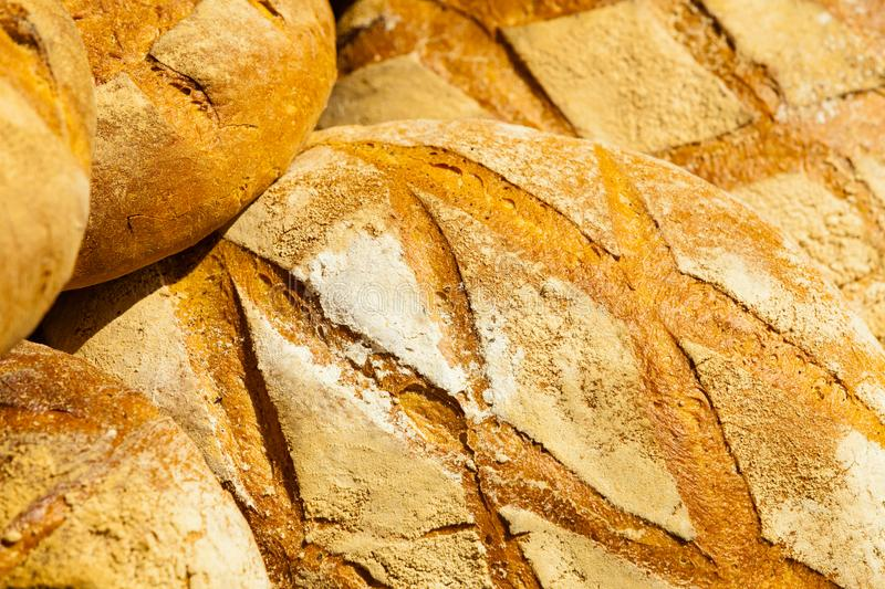Many brown rustic fresh rye bread loaves as food background. Many rustic baked traditional rye bread loaves on a market stall outdoor. Food background stock image