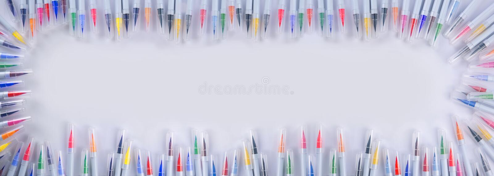 Many  brush pens and markers of different colors and shades are around the white sheet of the album stock photos