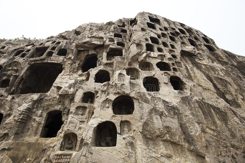 Many buddhist statues are carved into a rock cave. World cultural heritage, longmen grottoes, historical sites, ancient China, buddhist shrines stock photos