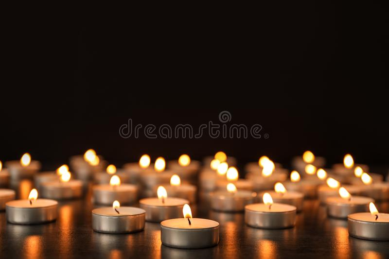 Many burning candles on table against dark background. royalty free stock photo