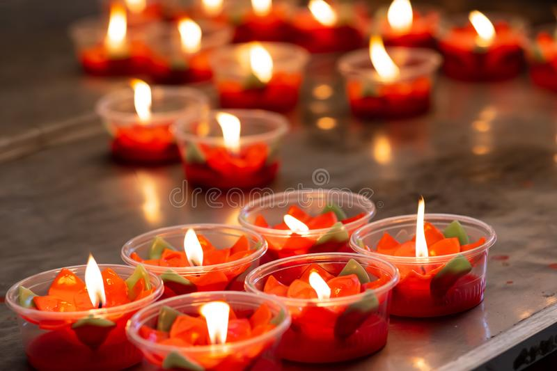 Many burning red flower candles cup at chinese temple stock image