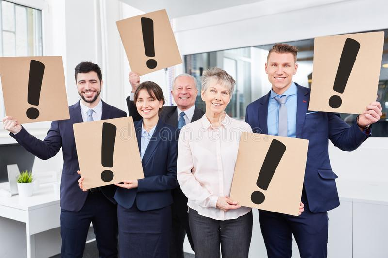 Many business people hold exclamation mark signs stock photos