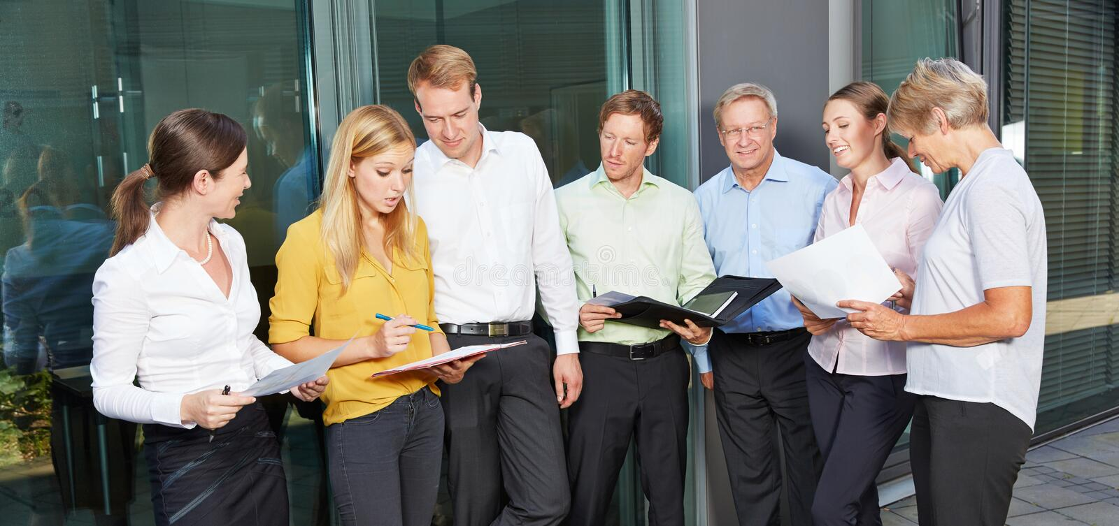 Many business people standing outside the office stock images