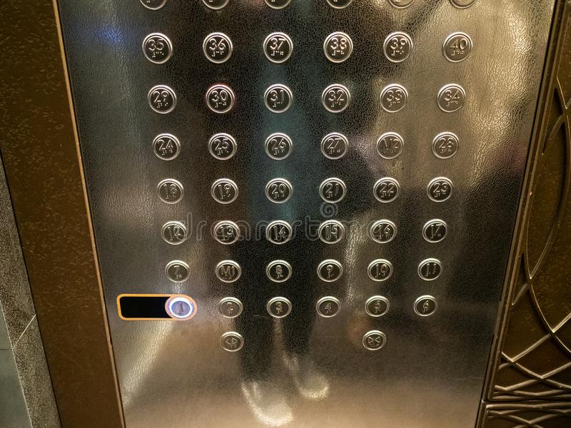 Many buttons in elevator of high-rise building. Panel with many buttons in modern passenger elevator of high-rise building stock photography