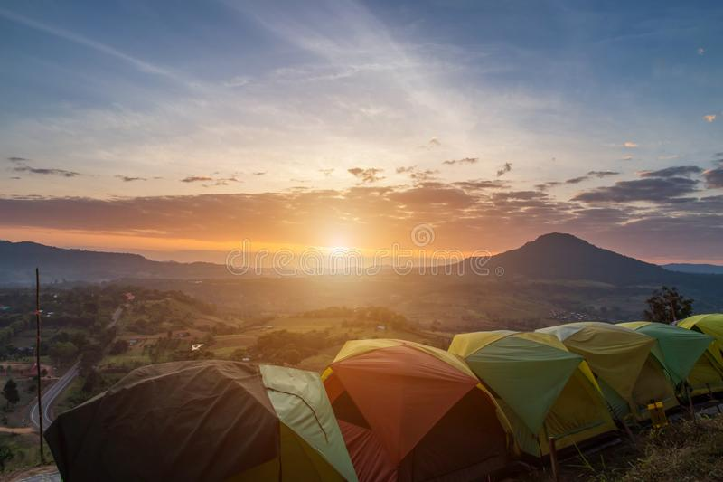 Many camping tent on green field near forest during dramatic sunrise at summer misty morning,Concept of outdoor camping adventure royalty free stock photography