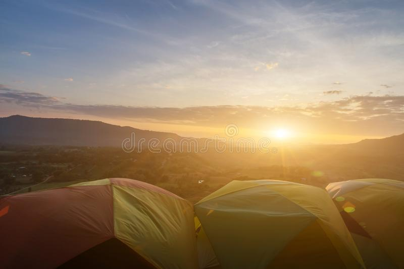 Many camping tent on green field near forest during dramatic sunrise at summer misty morning,Concept of outdoor camping adventure royalty free stock image