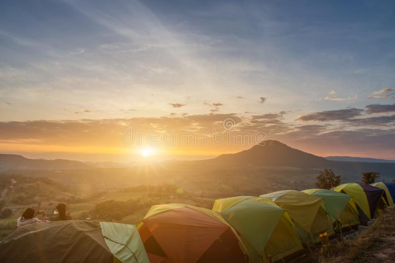 Many camping tent on green field near forest during dramatic sunrise at summer misty morning,Concept of outdoor camping adventure stock photo