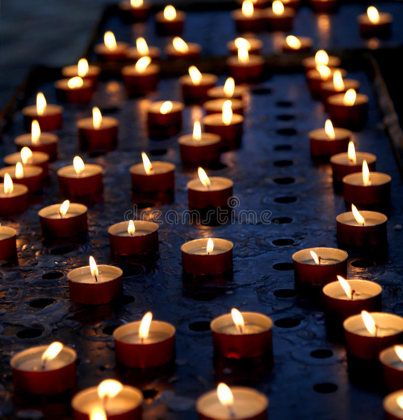 Many candles in a church for the prayers of the faithful. With flame royalty free stock image