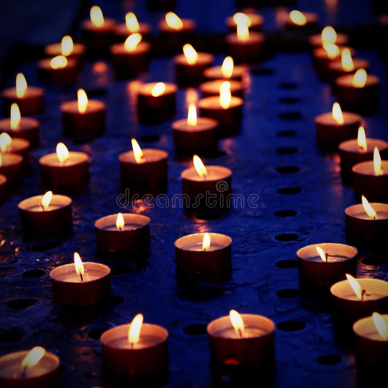 Many candles in a church for the prayers of the faithful with vi. Many candles in a church for the prayers of the faithful with flame with vintage effect stock photography