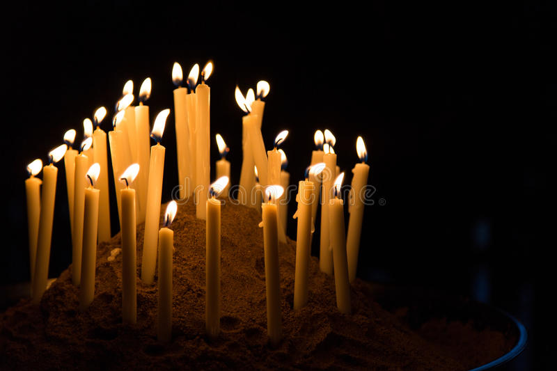 Many candles give warm yellow light in black background stock photography