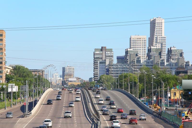 Many cars goes on bridge in large city royalty free stock image