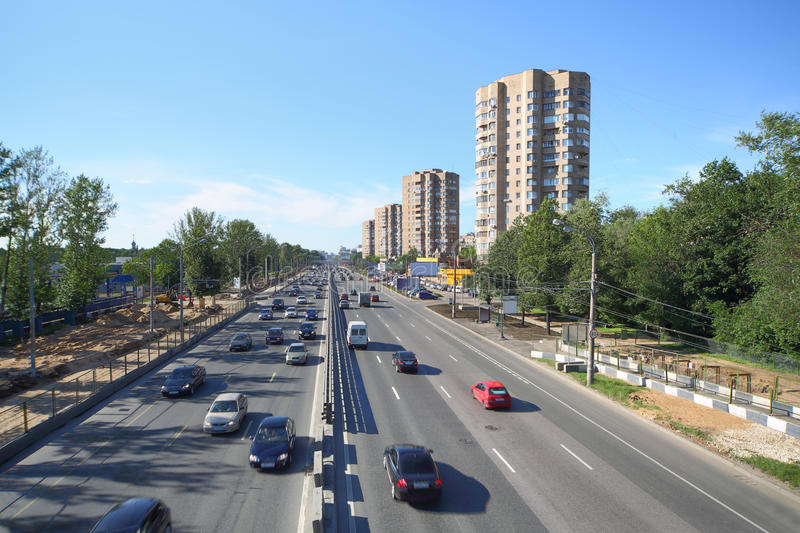 Many cars goes on wide road in large city stock photos