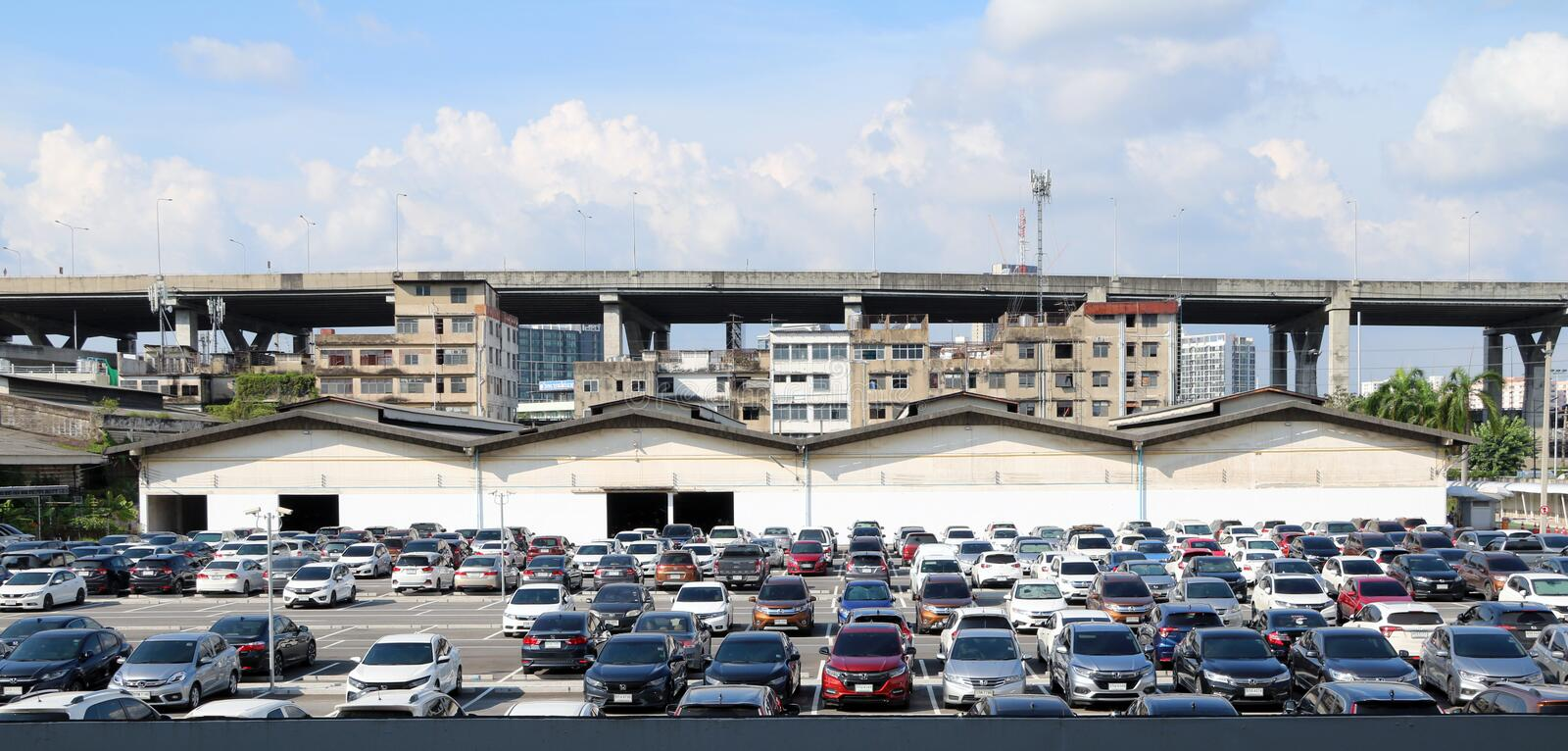 Many cars are parked at the outdoor parking lot with garage building and taller building, Expressway and blue sky. Bang Na, Bangkok, Thailand, Oct 16, 2018 stock images