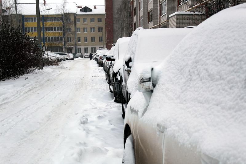 Many cars are standing in the parking lot near the apartment building under the snow. Snow, car, covered, weather, cold, parking, winter, blizzard, lot, season stock photography