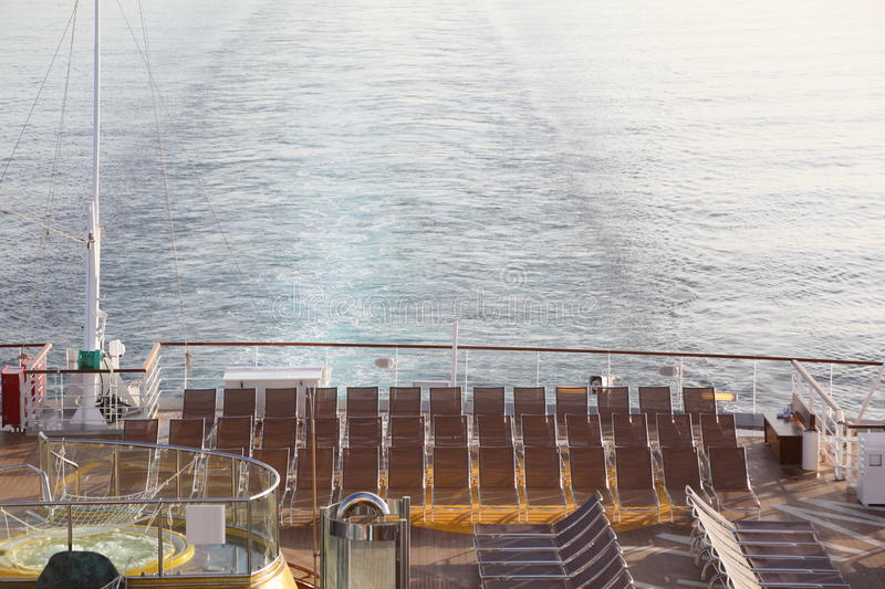 Many chaise longues on deck of cruise ship