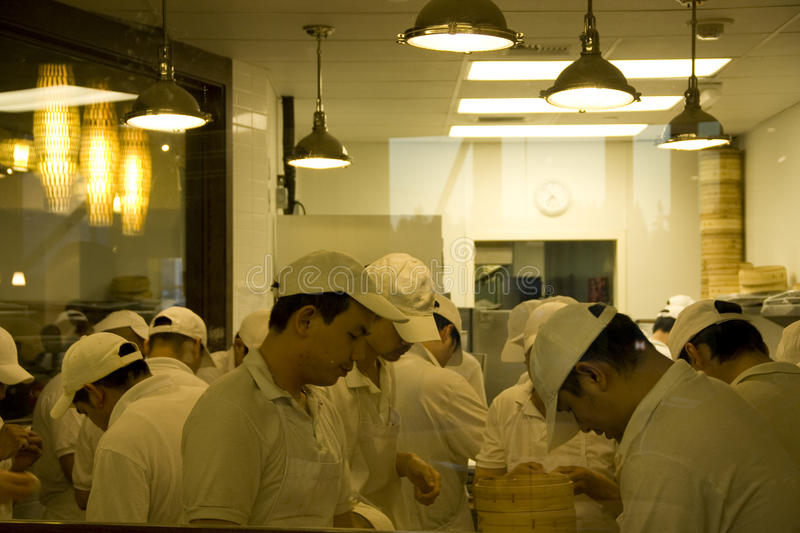 Busy chefs in chinese restaurant kitchen. Many chefs were busy making dumplings (Shanghai Xiaolongbao) in a Chinese restaurant. Ding Tai Feng Bellevue royalty free stock photos