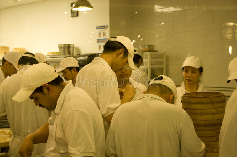Busy chefs in chinese restaurant kitchen. Many chefs were busy making dumplings (Shanghai Xiaolongbao) in a Chinese restaurant. Ding Tai Feng Bellevue royalty free stock images