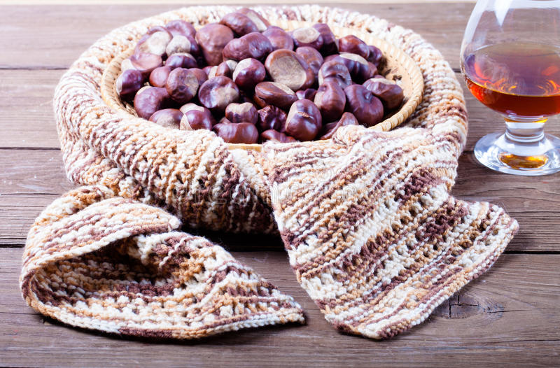 Many chestnuts in a knitted scarf and cognac in a glass on old w stock photos