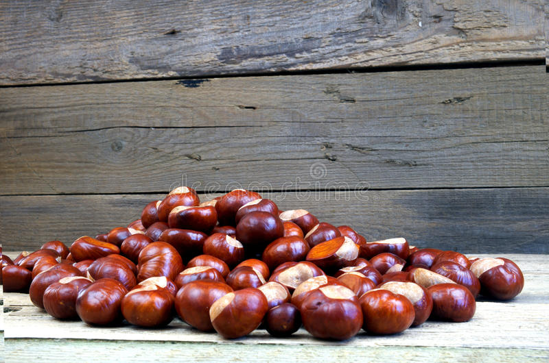 Many chestnuts on a wooden table royalty free stock photos