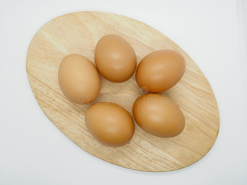 Many Chicken Brown Eggs on the Chopping board with white background stock photos