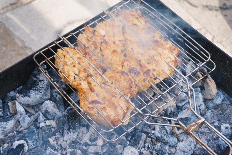 Many chicken roast meat pieces with onion on a grill royalty free stock photo