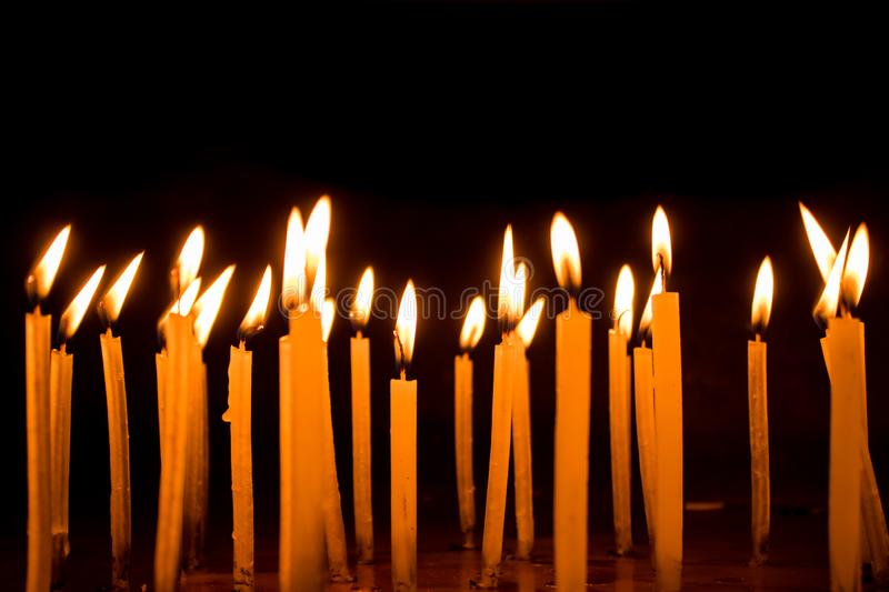 Many christmas candles burning at night on the black background stock images