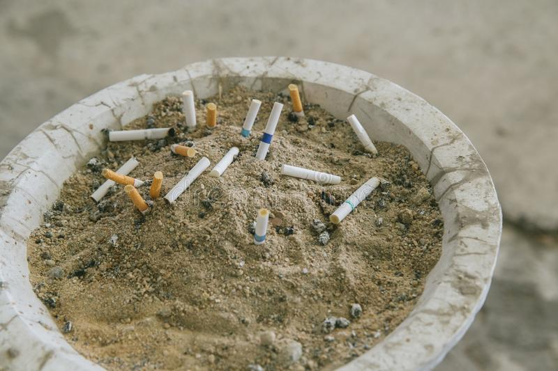 Many cigarette stub in sand ashtray. The rest of cigarettes in the ashtray. There are many types of cigarette stub on the sand in. The ashtray. A cigarette is royalty free stock images