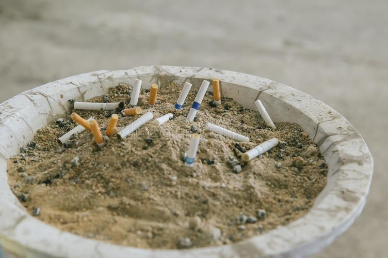 Many cigarette stub in sand ashtray. The rest of cigarettes in the ashtray. There are many types of cigarette stub on the sand in. The ashtray. A cigarette is royalty free stock photos