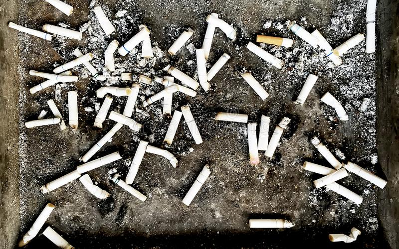 Many cigarette stubs on an ashtray stock photo