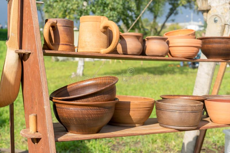 Many clay dishes on wooden shelf in Park. Pottery fair. Potter`s craft. Kitchen utensils royalty free stock photo