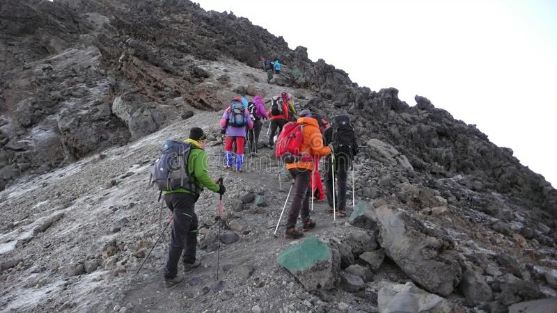 Many climbers hike towards the summit of Mount Meru in Arusha National Park in Tanzania. Arusha National Park, Kilimanjaro Province / Tanzania - 1. January 2016 royalty free stock images