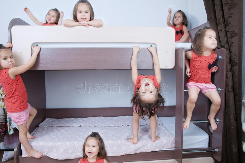 Many clone little girls on bund bed in child room in domestic life. identical child crowd. Child omnipresent and playing stock photos