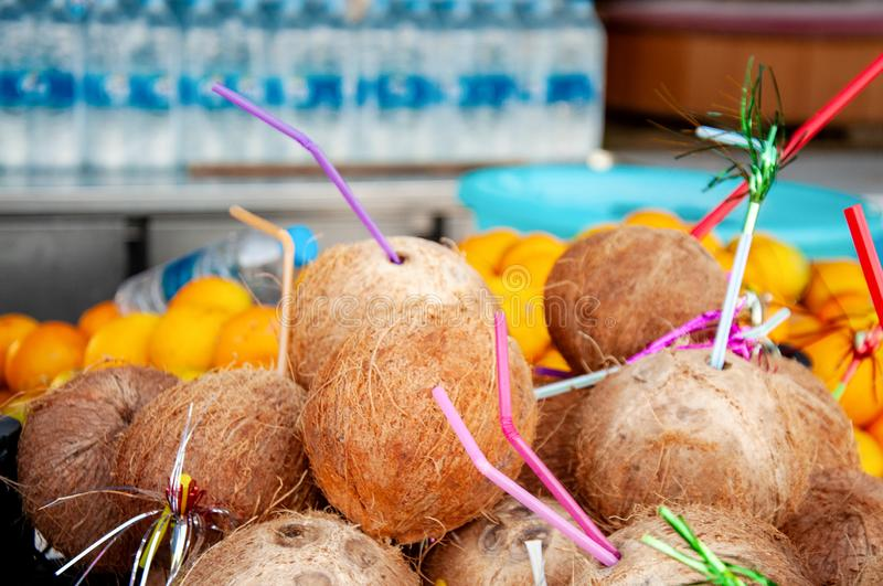 Many coconuts with a straw in a street shop. Exotic fruits. Interesting product. Fresh coconut is ready to eat. Many coconuts with a straw in a street shop stock images