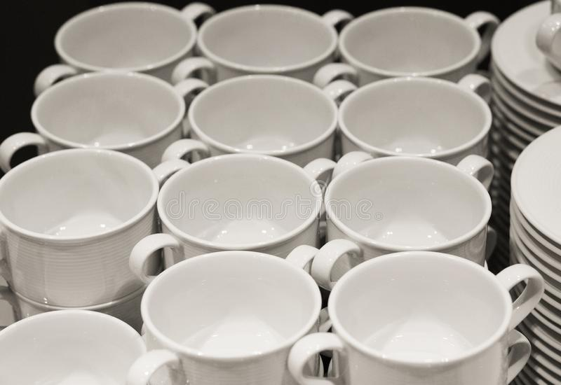 Many coffee cups are prepared for the event. Many white coffee cups are prepared in the event for those attending the party in the meeting room stock image