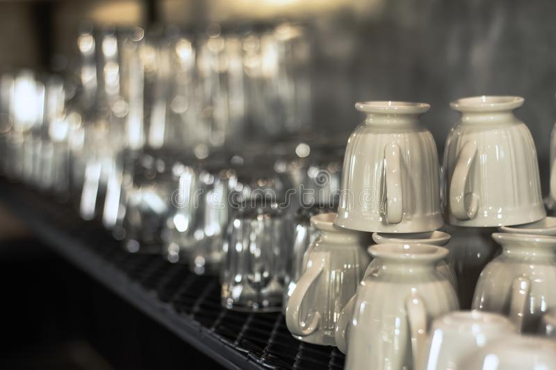 Many coffee mugs arranged on shelves, ready to serve. royalty free stock images