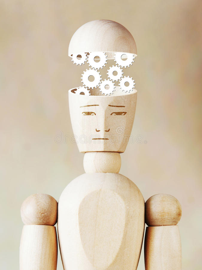 Many cogwheels working into the human head. Abstract image with wooden puppet stock photo