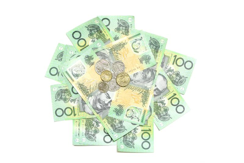 Many coins of Australian money on group of 100 dollar Australian notes pile background. On white background stock photos
