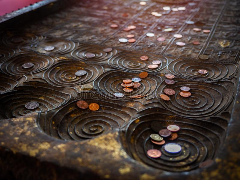 Many coins placed on replica of buddha footprint in the temple. Close-up many coins, Thai baht placed on replica of buddha`s footprint in buddhist church in royalty free stock photos